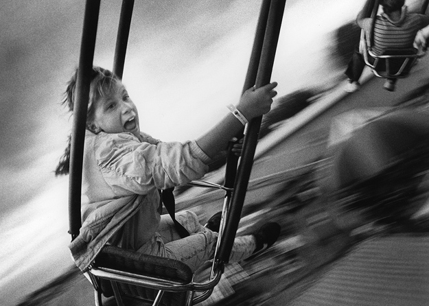 A young girl enjoys a carnival ride at the county fair.