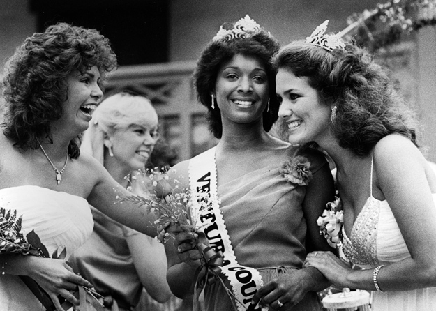 A fair queen is congratulated by fellow contestants.