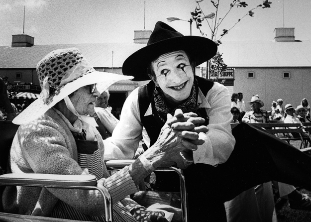 A mime provides entertainment to a senior citizen.