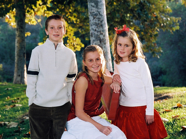 A traditional portrait pose of three siblings