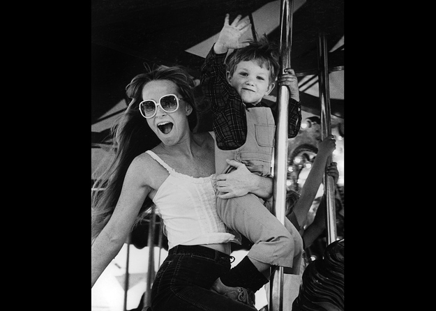 A woman and her nephew enjoy a Merry-go-round ride.