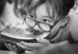 A youngster partakes in a watermelon contest.