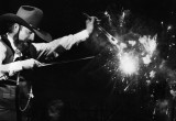 Charlie Daniels' fiddle is seeming ablaze.  This is a double exposure by superimposing a fireworks photo over his fiddle.