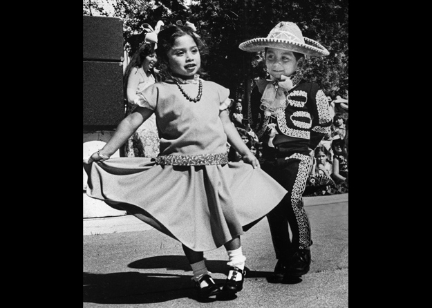 Two cute kids dance at a Cinco de Mayo celebration.
