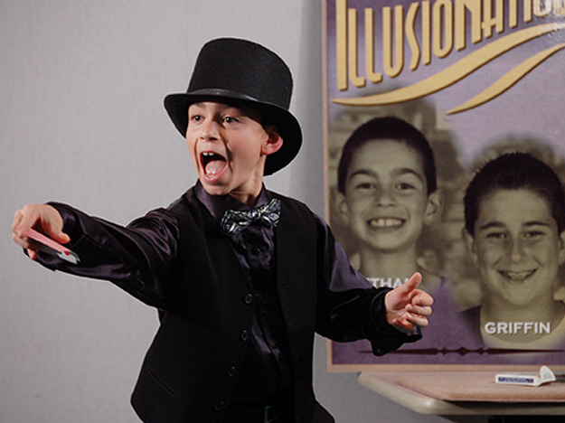 A young magician excites the crowd with a card illusion.