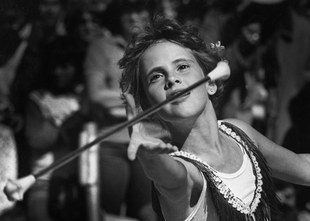 A young baton twirler performs during a city's annual parade, (Gallup, NM - 1981).