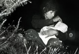 A mother sits among bushes in a field just north of the US-Mexico border