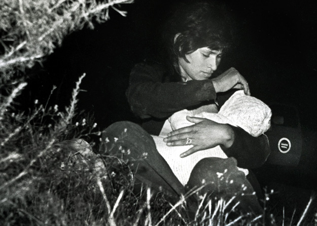 A mother sits among bushes with her child in a field just north of the US-Mexico border, (San Ysidro, CA - 1982).