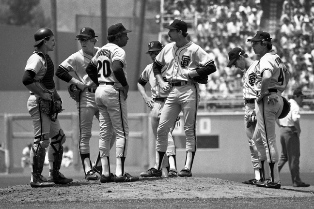 1983 - Manager Frank Robinson and his players have perplexed looks at the mound, versus the Dodgers.