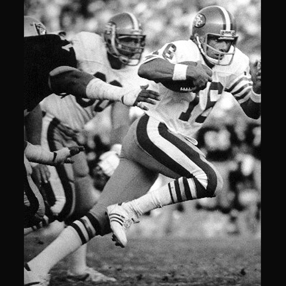 1983 - Joe Montana scampers around the left side of the line in a game against the L.A. Raiders.